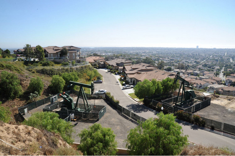 A residential neighborhood with oil derricks in Signal Hill, CA. Photo courtesy of the Center for Land Use Interpretation, Los Angeles.