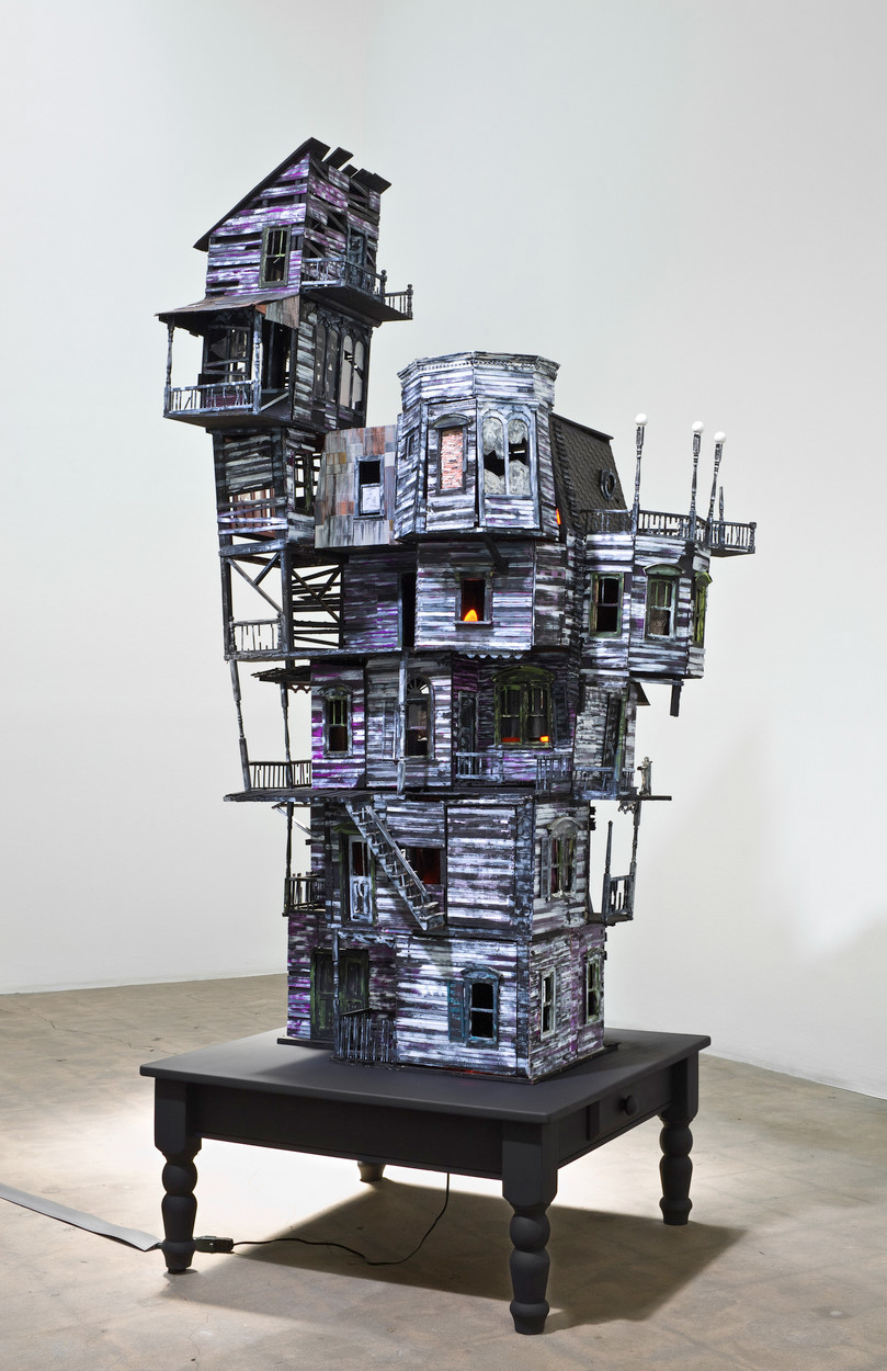 Richard Hawkins, <em>The Last House</em>, 2010. Altered dollhouse, lighting, and table, 89 x 36 x 36 in.