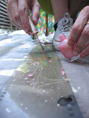 Jennifer West applying nail polish to film strips for <em>Lavender Mist Film/Pollock Film 1 (70mm film leader rubbed with Jimson Weed Trumpet flowers, spraypainted, dripped and splattered with nail polish, sprayed with lavender mist air freshener)</em>, 2009. 46 sec. Photo: Finn West.