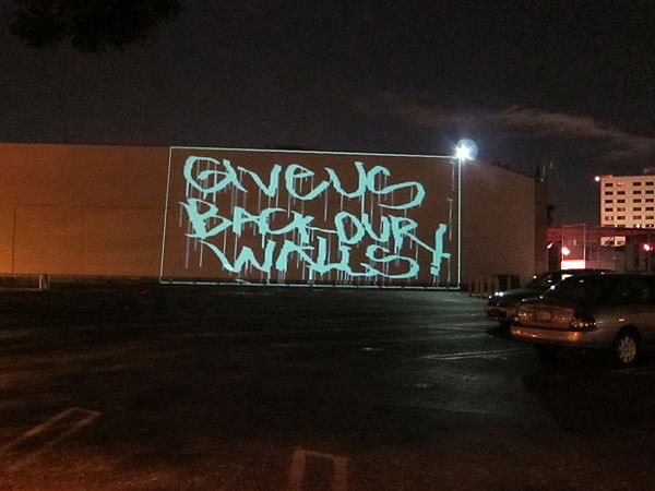 A guerrilla performance at MOCA's Geffen Contemporary in early January used projected graffiti to protest the whitewashing of a mural by Blu. Photo: Deborah Vankin.