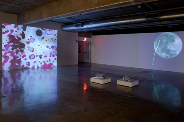 "Installation View of ""Perspectives 171: Jennifer West,"" Contemporary Art Museum, Houston, 2010. From left: <em>Lavender Mist Film/Pollock Film 1 (70mm film leader rubbed with Jimson Weed Trumpet flowers, spraypainted, dripped and splattered with nail polish, sprayed with lavender mist air freshener)</em>, 2009. 46 sec. <em>Shred the Gnar Full Moon Film Noir (35mm film print and negative shredded and stomped on by a bunch of Snowboarders and a few Skiers getting ginormous catching air during Aspen Big Air Competition and Fallen Friends Event– marked up with blue course dye - sprayed with Diet Coke, Bud Lite & Whiskey - taken hot tubbing with Epsom salts, rubbed with Arnica, K-Y Jelly, butter and Advil – full moon shot by Peter West)</em> 2010. 5 min, 9 sec. Photo: Rick Gardner."